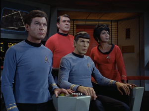"DeForest Kelley as Leonard ""Bones"" McCoy, James Doohan as Montgomery ""Scotty"" Scott, Nichelle Nichols as Lieutenant Uhura, Leonard Nimoy as Mr. Spock."
