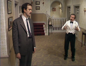 "John Cleese as Basil Fawlty and Andrew Sachs as Manuel, Fawlty Towers, ""The Psychiatrist"""