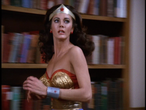 Wonder Woman runs in front of a book case