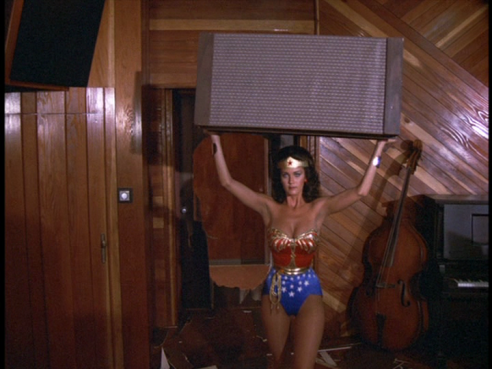 Wonder Woman carries the speaker toward Carl.